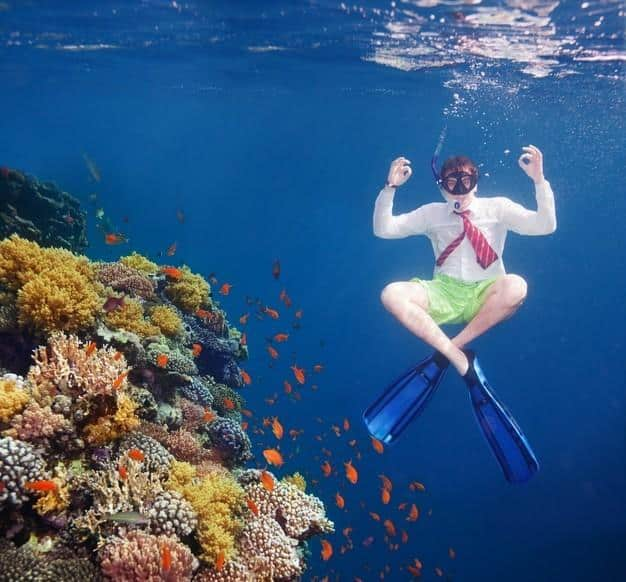 White collar worker man meditating underwater close to coral water with red tie and white shirt