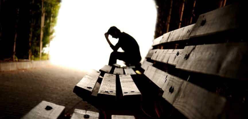 homem deprimido sentado em banco