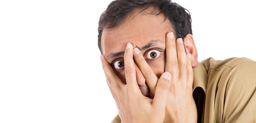 homem escondendo o rosto de medo