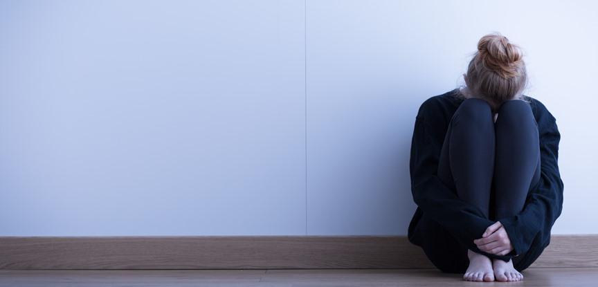 mulher sentada no chão chorando