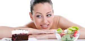 mulher escolhendo entre pedaço de bolo e salada