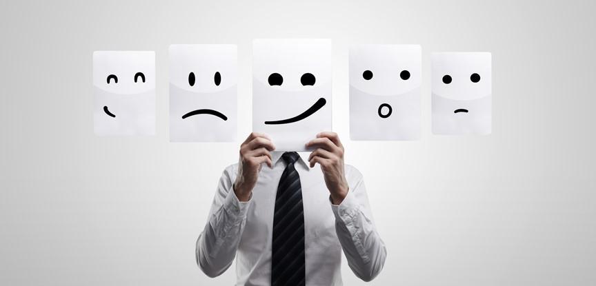 homem segurando desenho de diversos rostos com emoções
