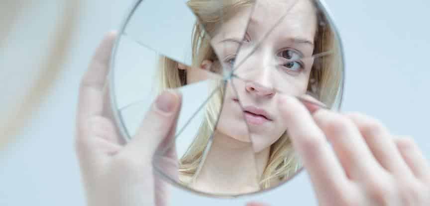 mulher olhando seu reflexo em espelho quebrado