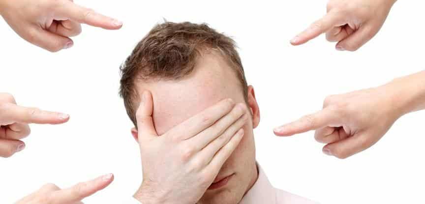 homem se escondendo de dedos apontando para seu rosto