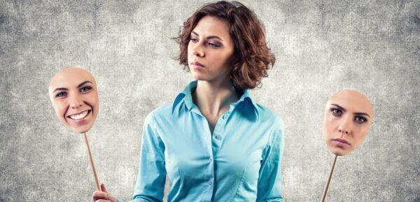 mulher olhando para suas máscaras que transmitem diferentes sentimentos