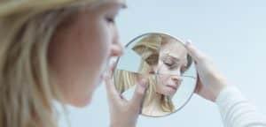 mulher olhando em espelho quebrado