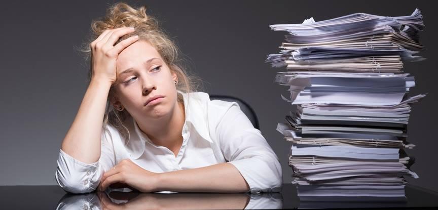 mulher cansada olhando para pilha de livros