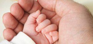 mão de pai segurando mãozinha de bebê