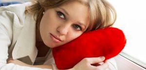 mulher triste segurando almofada em forma de coração