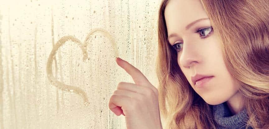 mulher infeliz desenhando coração na janela