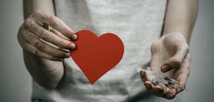 homem segurando coração de papel e seringas
