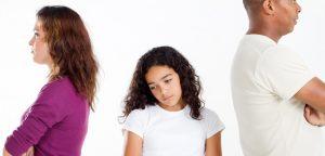 pais brigados com criança no meio triste