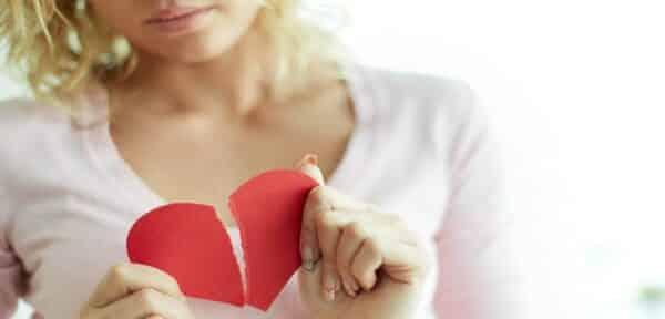 mulher segurando coração rasgado