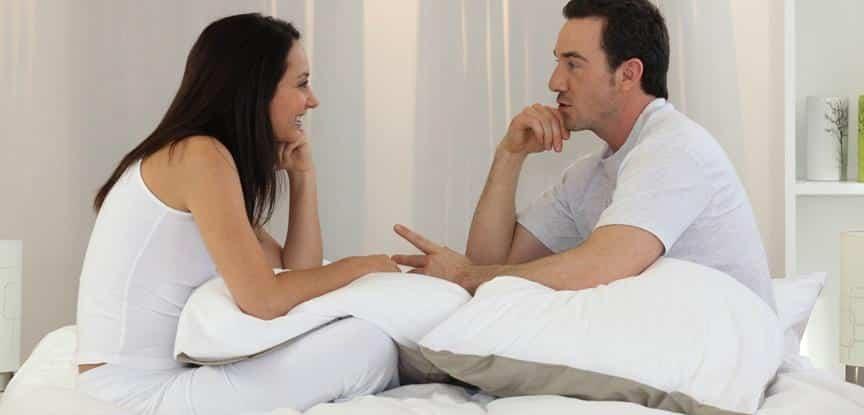 casal conversando sentado na cama