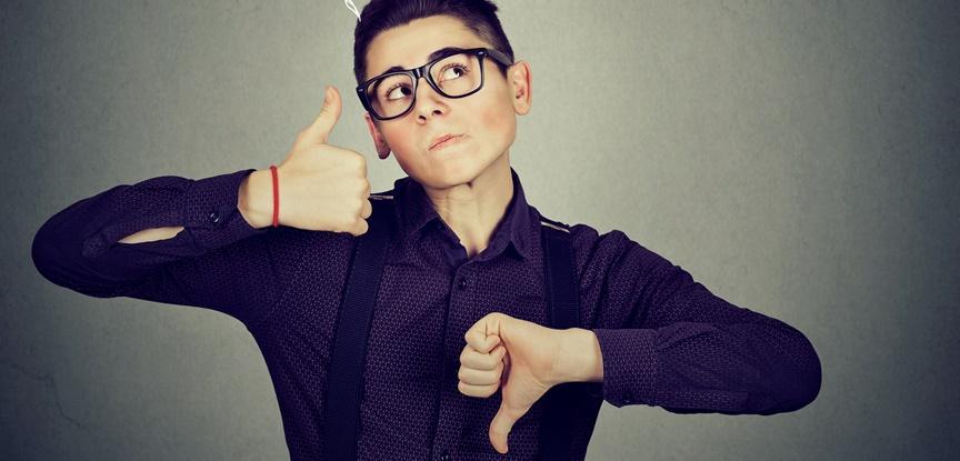 menino com as mãos fazendo sinais de positivo e negativo