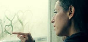 mulher sozinha desenhando coração na janela