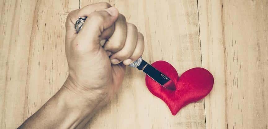 pessoa segurando faca em cima do coração de papel