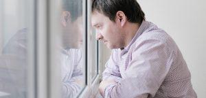 foto de homem triste olhando pela janela