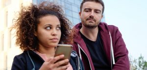 foto de homem tentando olhar o celular da mulher