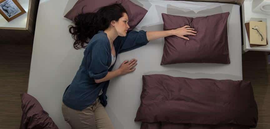 foto de mulher triste deitada na cama