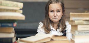 foto de menina com cara de choro ao lado de livros
