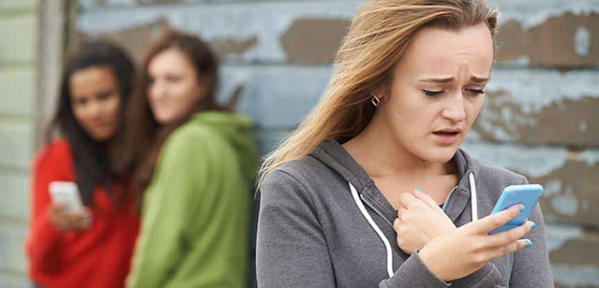 Foto de adolescente sendo intimidada por mensagem de texto