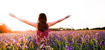 Menina livre, aproveitando a natureza num lindo campo florido