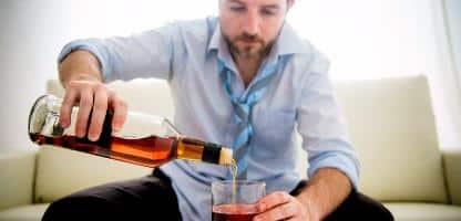Empresário vestindo camisa azul bêbado na mesa no fundo branco Empresário vestindo camisa azul bêbado na mesa no fundo branco
