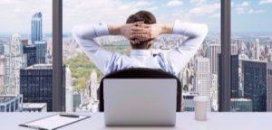 Vista traseira do empresário relaxante com as mãos cruzadas atrás da cabeça, quem está a olhar para o parque Central. Panorâmica de escritórios ou local de trabalho, com vista para cidade de Nova York