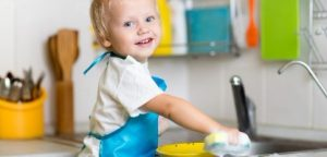 Filho de criança lavando pratos na cozinha. Garotinho se divertindo com a ajudar a sua mãe com o trabalho doméstico Filho de criança lavando pratos na cozinha. Garotinho se divertindo com a ajudar a sua mãe com o trabalho doméstico