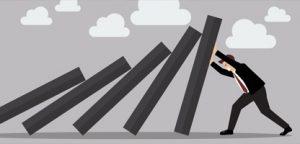 Empresário, esforçando-se contra o convés queda de peças de dominó