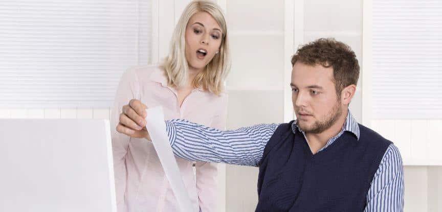 Descontrole emocional: Empresário chocado e sentado no controlar finanças de mesa e para fora