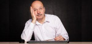O homem idoso no trabalho sonhadora parece afastado durante uma pausa O homem idoso no trabalho sonhadora parece afastado durante uma pausa