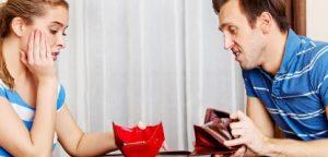 Casal com conta conjunta preocupado sentado à mesa com carteiras vazias