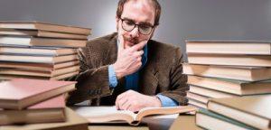 Jovem professor arredondado com pilhas de livros sobre gestão de carreira