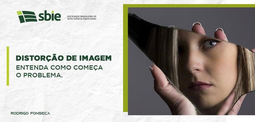 Na imagem, uma mulher olha seu reflexo em um pedaço de espelho quebrado, com uma feição de desconfiança.
