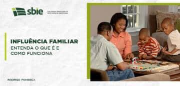 Na imagem há uma família feliz reunida em volta de uma mesa, fazendo referência ao tema influência familiar